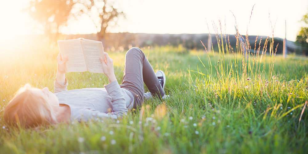 Teenager reading a book in a field